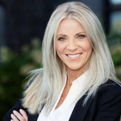 Portrait Of A Mature Blonde Businesswoman Smiling. Outside the office. She is happy, arms crossed